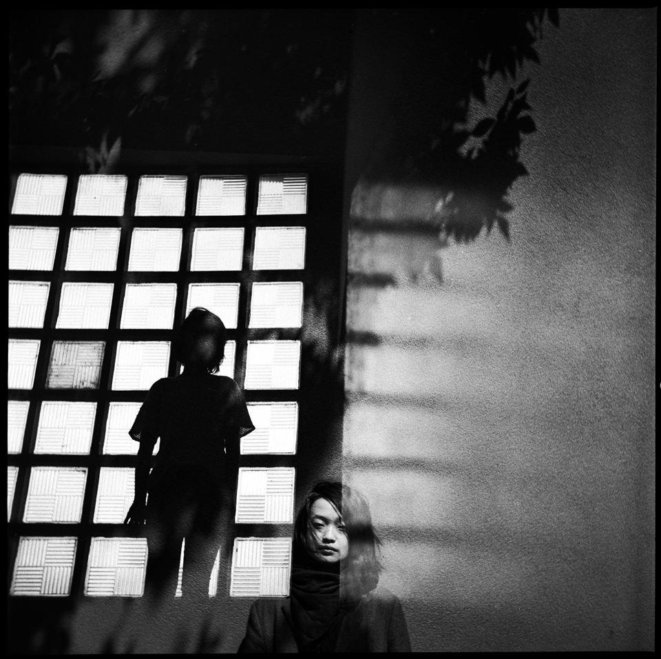 Eine Doppelbelichtung einer Frau vor einem Fenster
