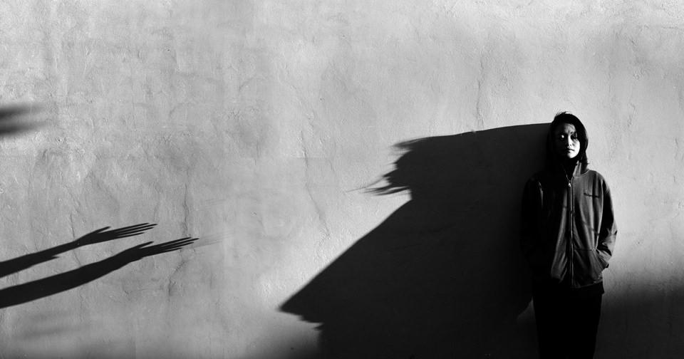 Eine Frau an steht an einer Wand und wird von Schattenarmen empfangen