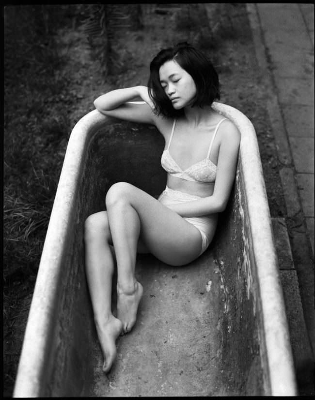 Eine Frau liegt in einer leeren Badewanne