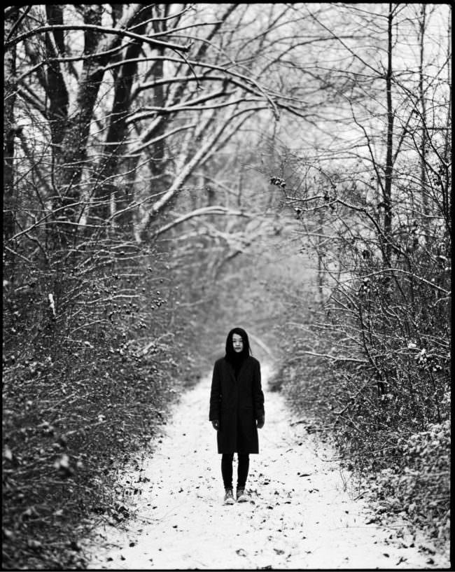 Eine dunkel gekleidete Frau steht auf einem verschneiten Waldweg