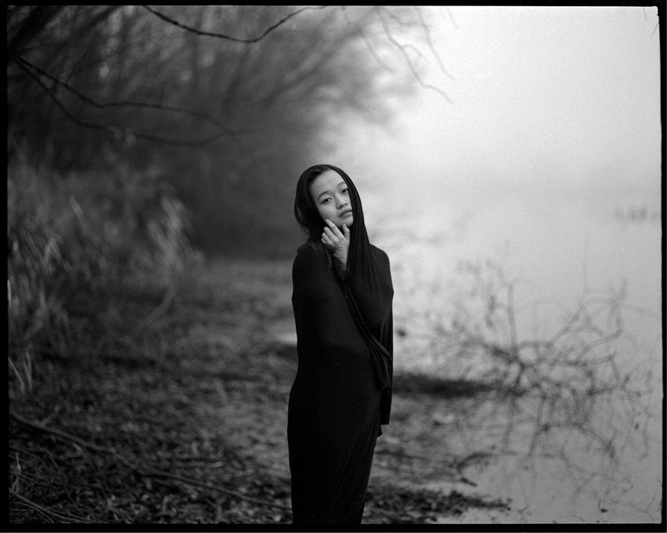 Eine in ein dunkles Tuch gehüllte Frau steht an einem nebligen Flussufer