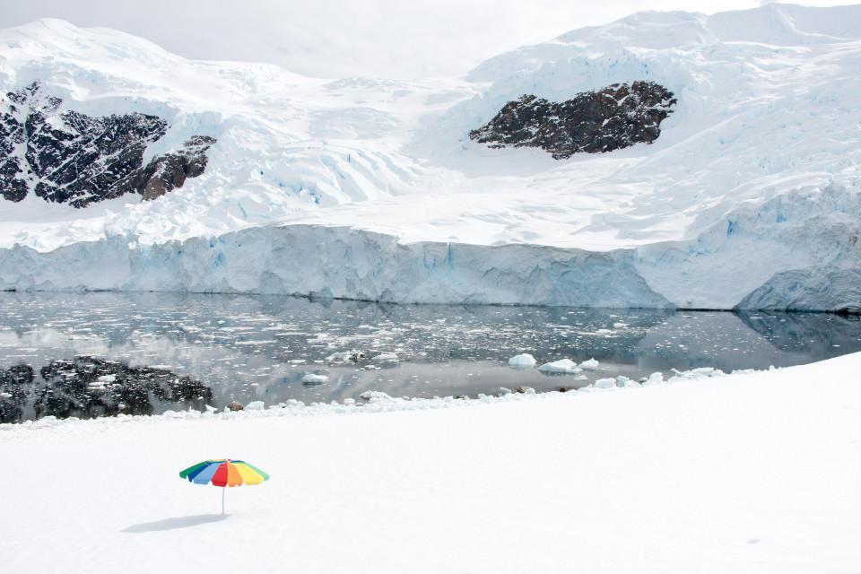 Ein bunter Sonnenschirm steht auf schneebedecktem Boden.