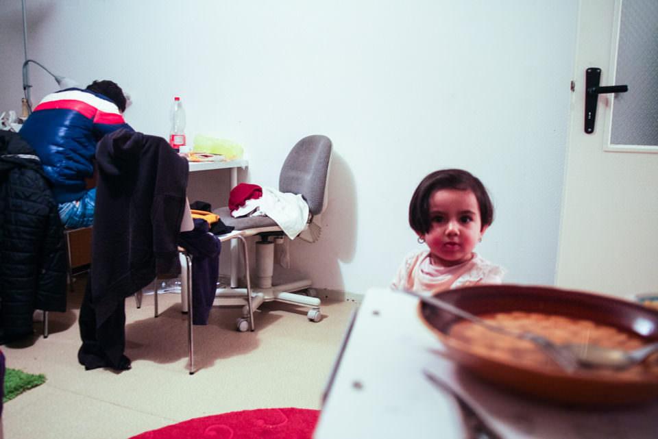 Ein Kind steht in einem Raum vor einem Tisch