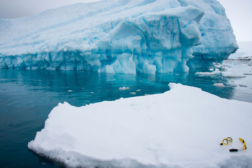 Ein Schnorchel und eine Taucherbrille liegen auf einer Eisscholle.
