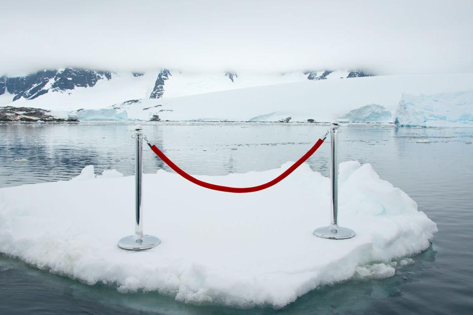 Ein rotes Absperrseil steht auf einer Eisscholle im Meer.