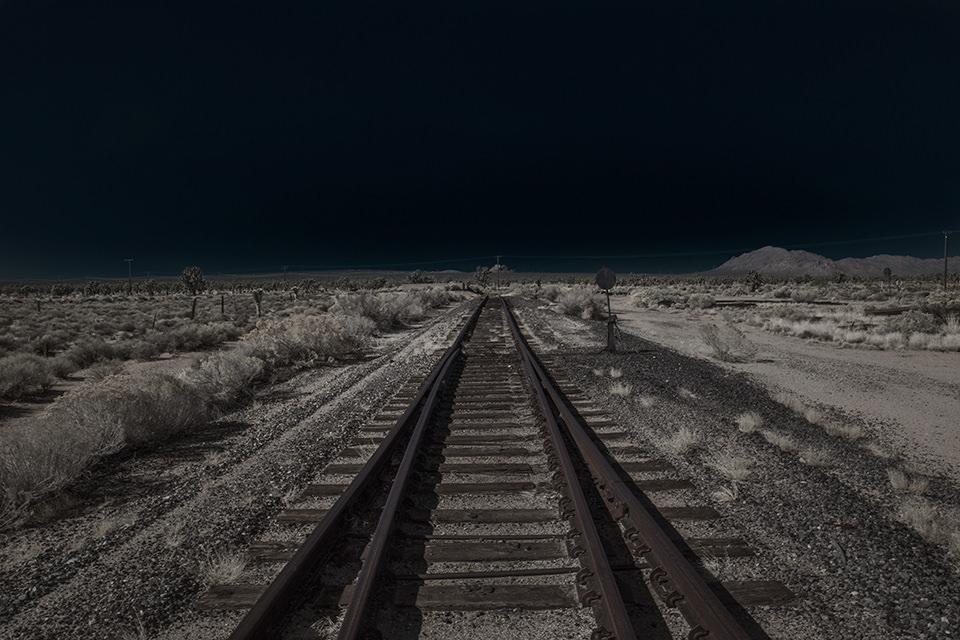 Eine ausgeleuchtete Wüstenlandschaft mit Gleisen, die zum Horizont führen.