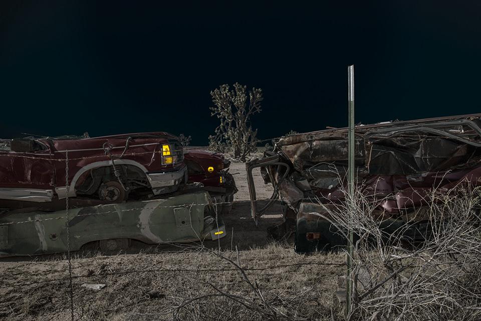 Eine ausgeleuchtete Wüstenlandschaft mit zwei rostigen Autos.