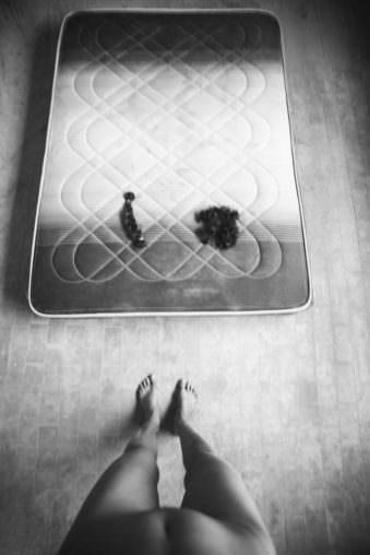 Füße vor einer Matratze mit abgeschnittenen Zöpfen darauf.
