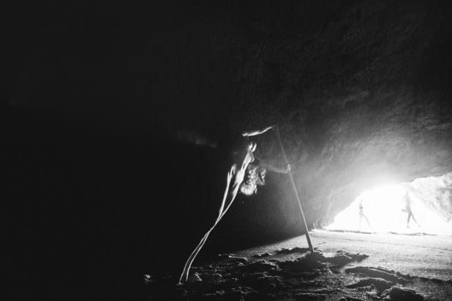 Eine Frau in einer Höhle, davor vorbeigehende Menschen.