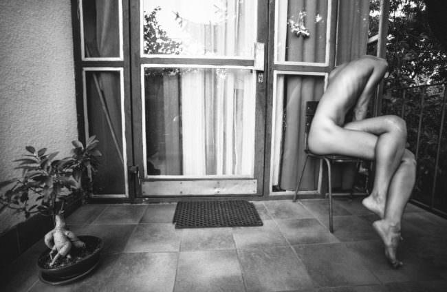 Wurzel, Terrasse, ein kopfloser nackter Mensch.