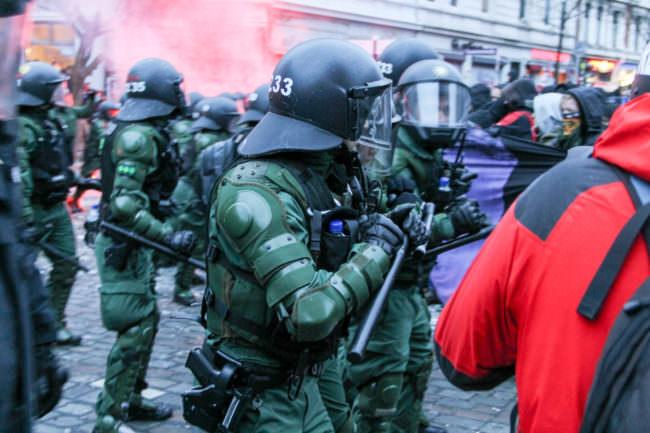 Polizisten und Demonstranten vor rotem Rauch