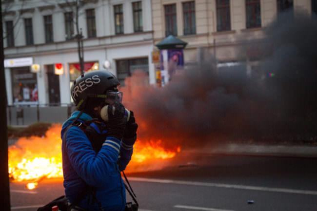Ein Demonstrant steht vor einer brennenden Barrikade