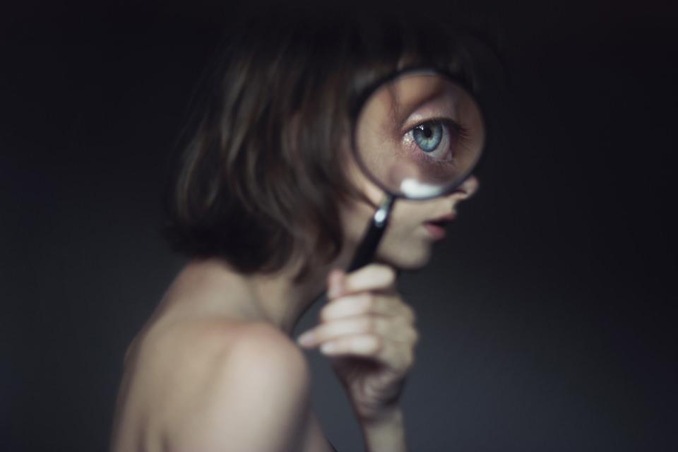 Eine junge Frau schaut durch eine Lupe