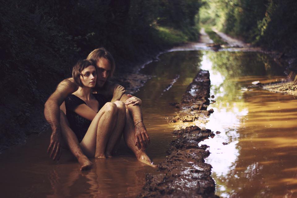 Zwei Personen sitzen in einer Pfütze