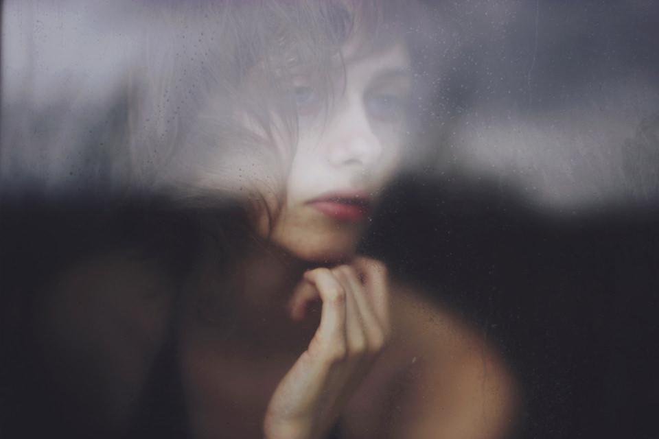 Portrait einer jungen Frau durch eine Scheibe