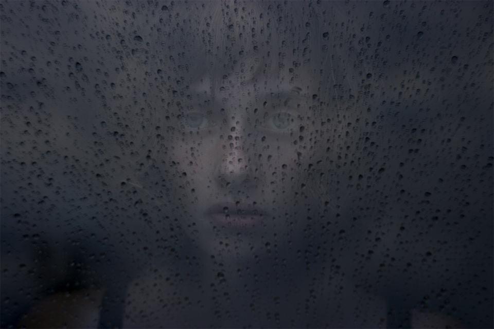 Portrait einer jungen Frau durch eine nasse Scheibe