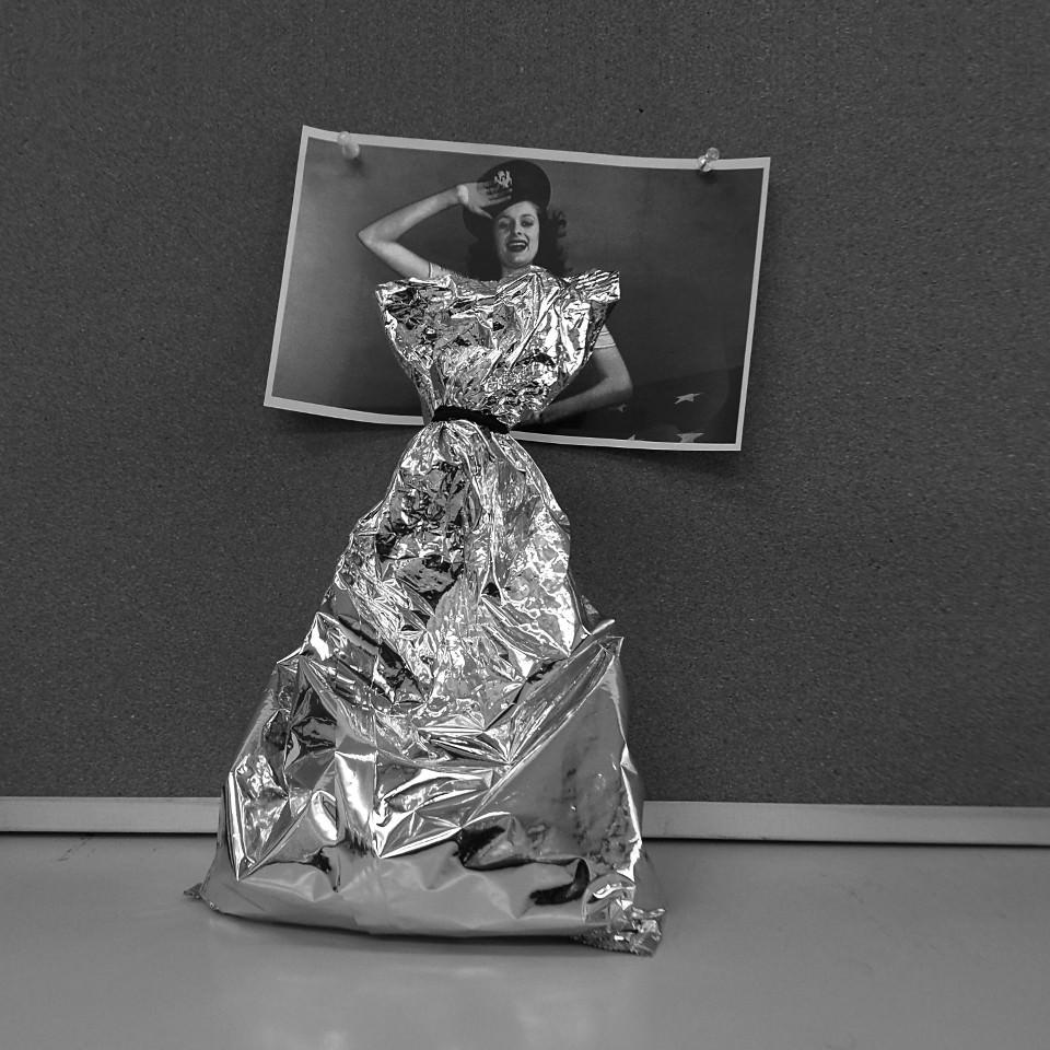 Ein Foto einer Frau klebt über einer Alutüte.