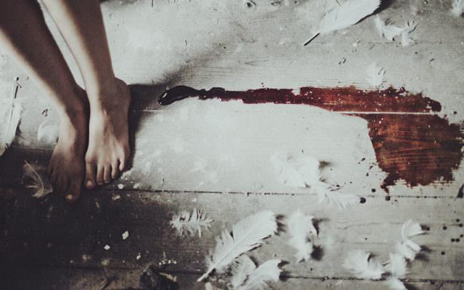 Nackte Füße, weiße Federn und eine Blutspur ergießt sich über den Holzboden.