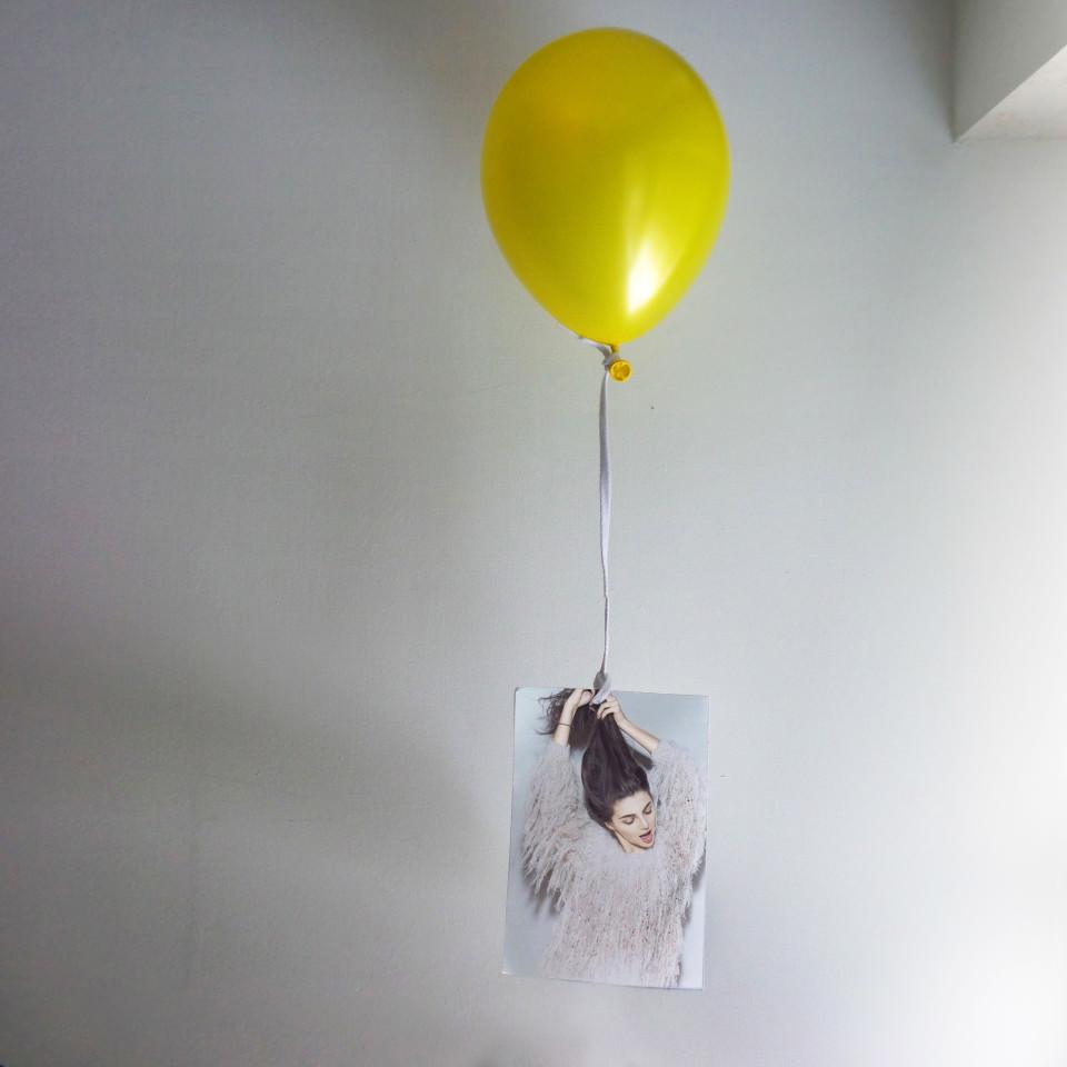 Ein gelber Luftballon hängt an einem Foto einer Frau.