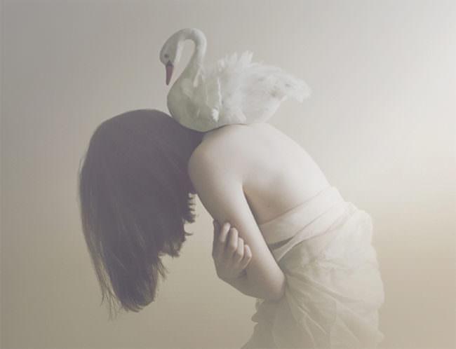 Ein Stoffschwan liegt auf den nackten Schultern eines Mädchens.