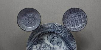 Drei blaugemusterte Teller liegen wie ein Kopf mit Ohren zusammen.
