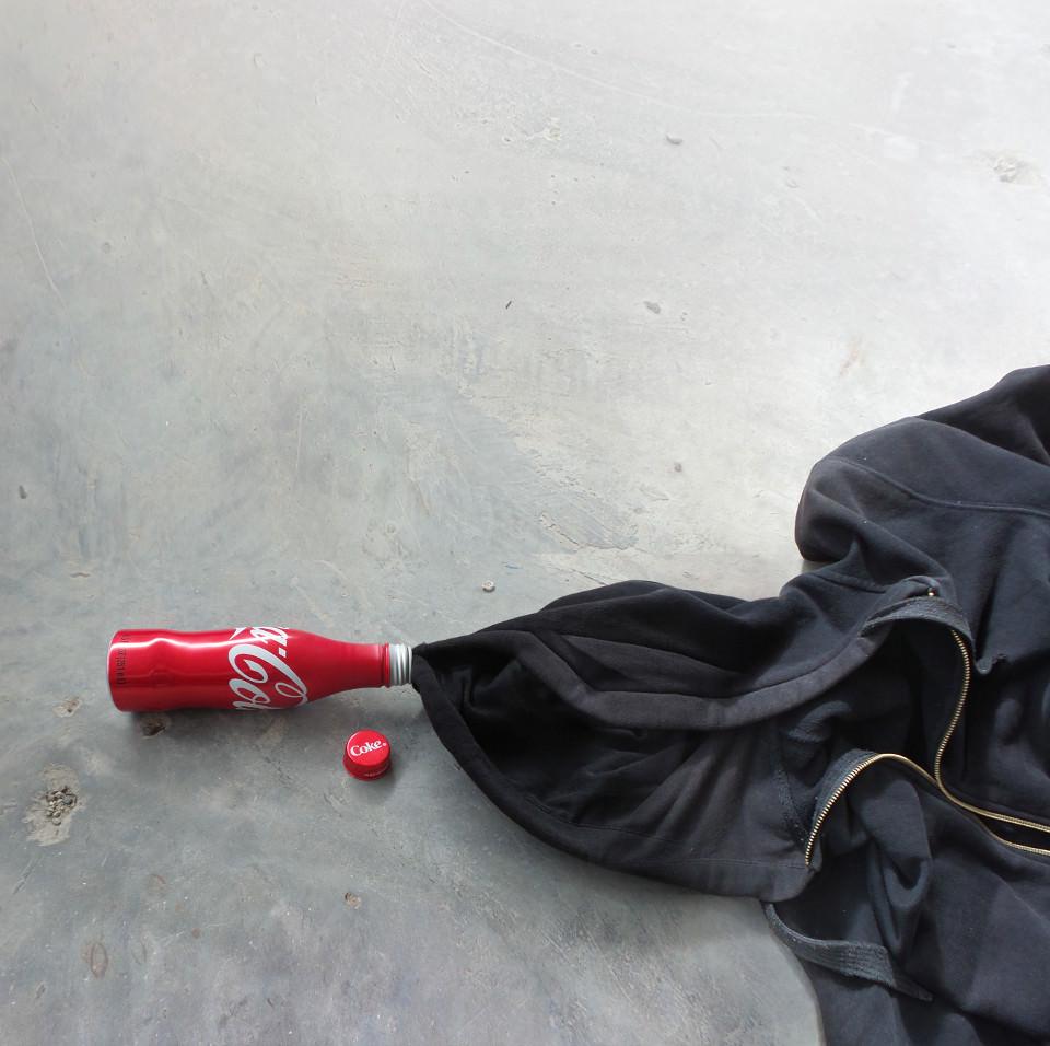 Aus einer Cola-Flasche schaut schwarzer Stoff heraus, als würde sie auslaufen.
