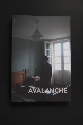 Buchcover mit den Worten Avalanche und einer Frau auf einem Bett sitzend.