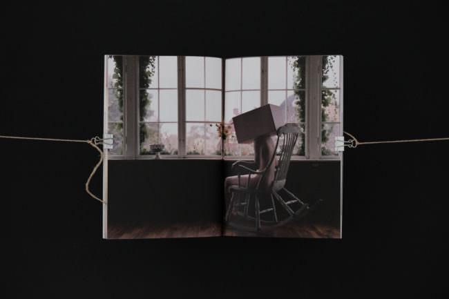 Eine Frau mit einem Kartonkopf sitzt in einem Schaukelstuhl.