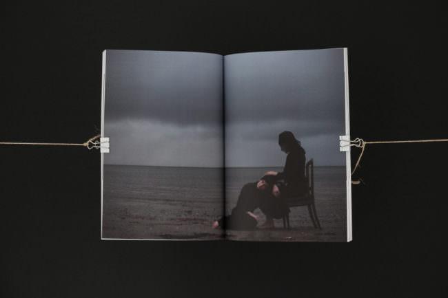 Eine verdunkelte Gestalt sitzt am Meer und hält den Kop einer zweiten Person auf ihrem Schoß.