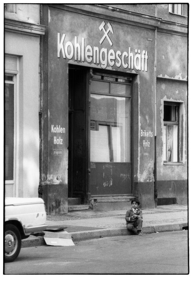Eine Junge sitzt auf dem Gehsteig an einer Straße.