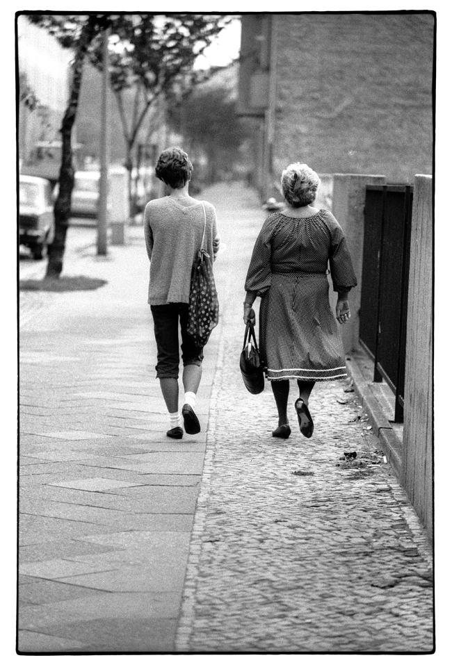 Zwei Personen gehen eine Straße entlang, man sieht ihren Rücken.