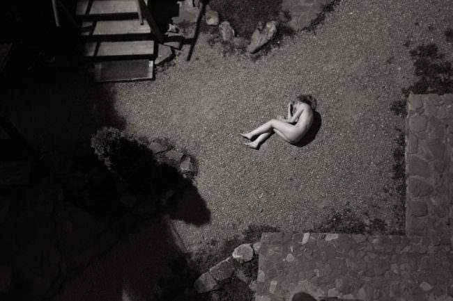 Eine Frau liegt nackt auf der Straße
