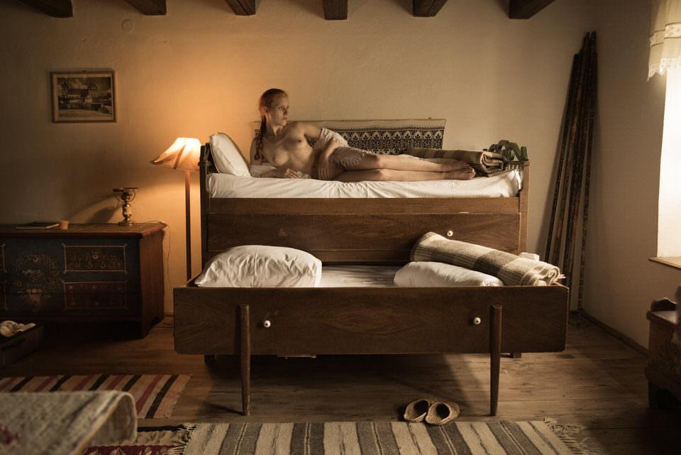 Eine Frau liegt nackt in einem altertümlichen Bett.