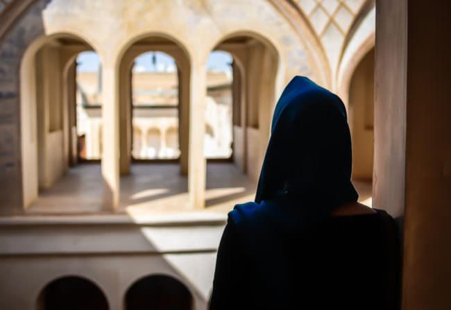 Eine Frau vor Bogentüren