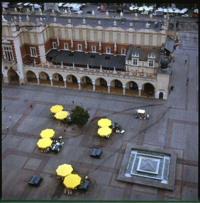 Ein Platz in der Stadt mit Sonnenschirmen.