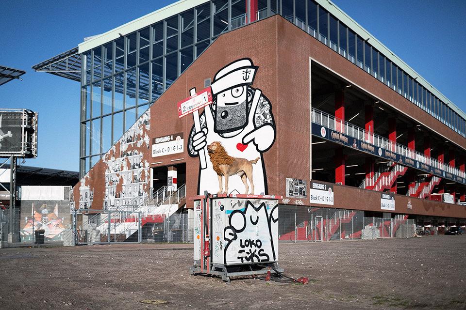 Ein Hund mit einer Löwenmähne steht vor einem großen Graffiti auf einem Stromkasten