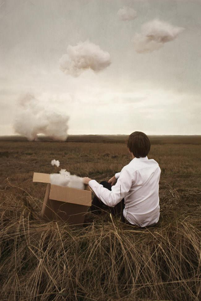 Mann sitzt neben einer Kiste aus der Wolken schweben