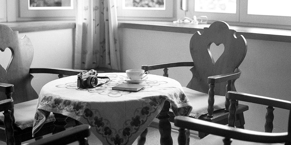 Kamera und Teetasse auf einem Kaffeetisch.