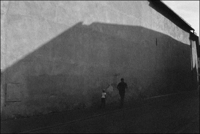 Ein Mann und ein Kind im Schatten der Wand.