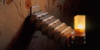 Verlängerungsstecker sind mehrfach eineinandergeklickt, an ihrem Ende leuchtet eine Lampe.