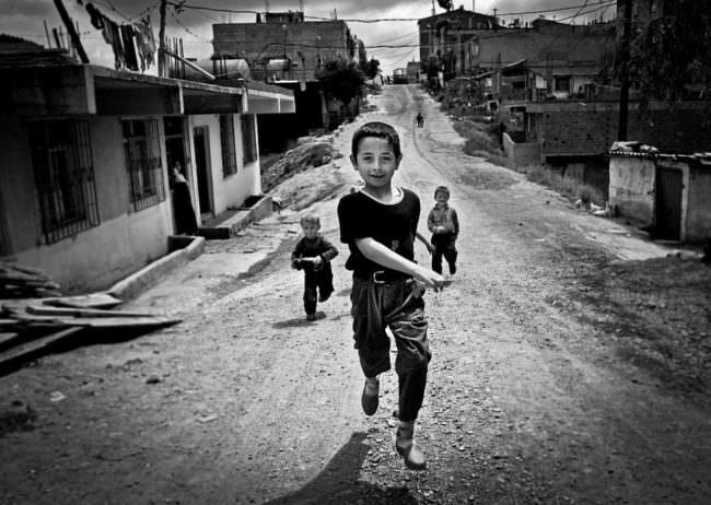 Mehrere Jungen laufen eine Straße entlang.
