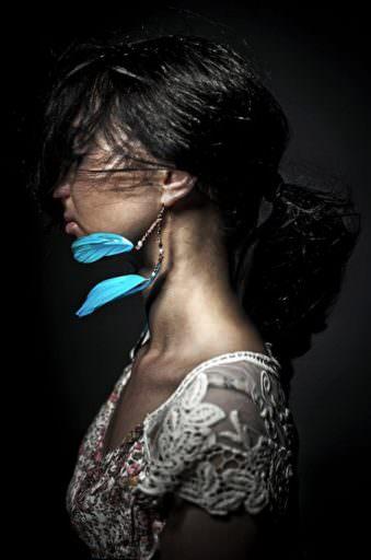 Seitliches Portrait einer Frau mit fliegenden blauen Feder-Ohrringen.