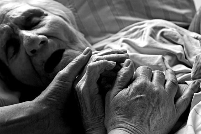 Zwei Hände halten die Hand einer im Bett liegenden alten Frau.