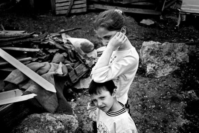 Zwei zusammenstehende Kinder vor einem Haufen Müll.