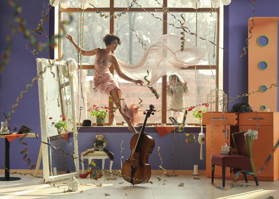 Eine Frau balanciert auf einer Viola vor einem Fenster