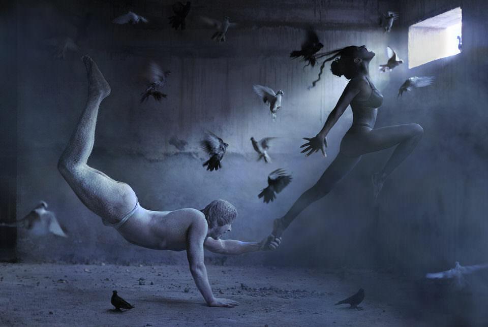 Ein Mann auf einer Hand stehend zieht eine fliegende Frau am Fuß
