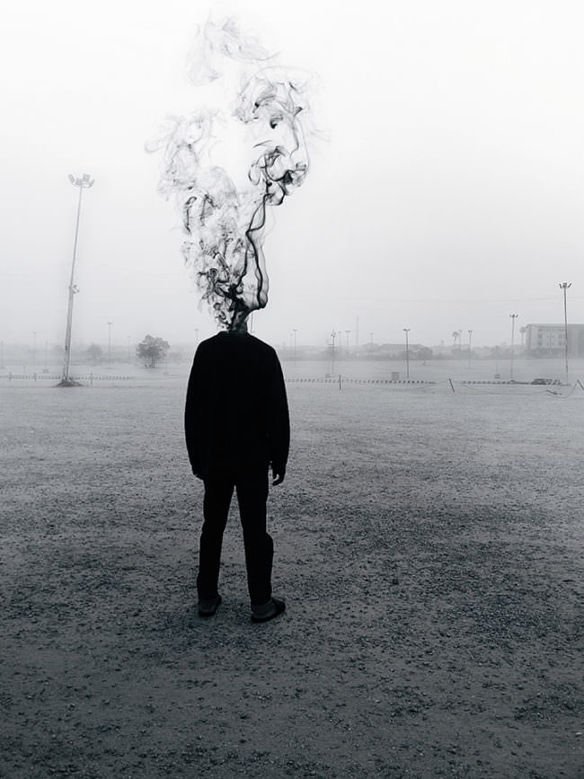 Eine Person steht auf einem Feld, anstatt eines Kopfes raucht sie aus dem Hals.