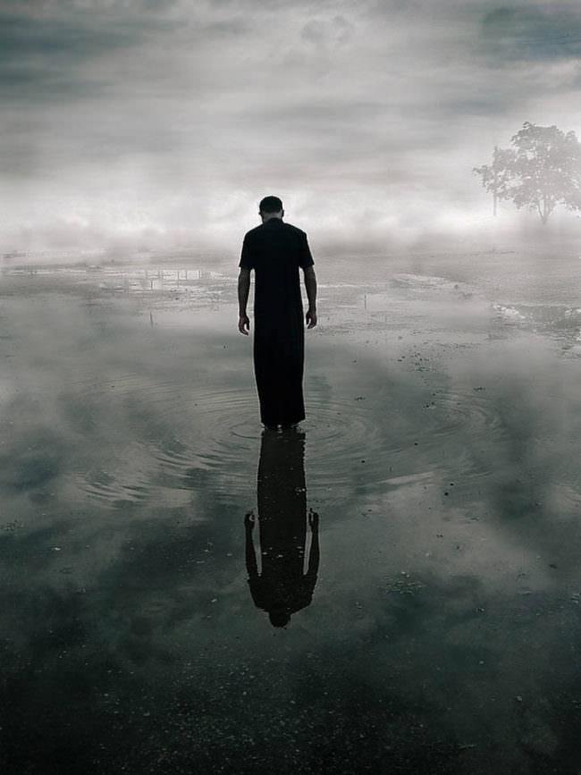 Eine Person steht im Wasser, Wolken spiegeln sich darin.