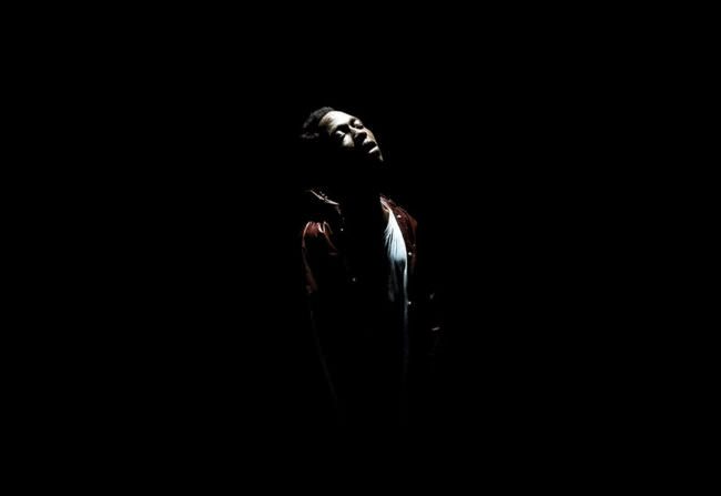 Eine Person steht in dunkler Umgebung unter einem Licht.