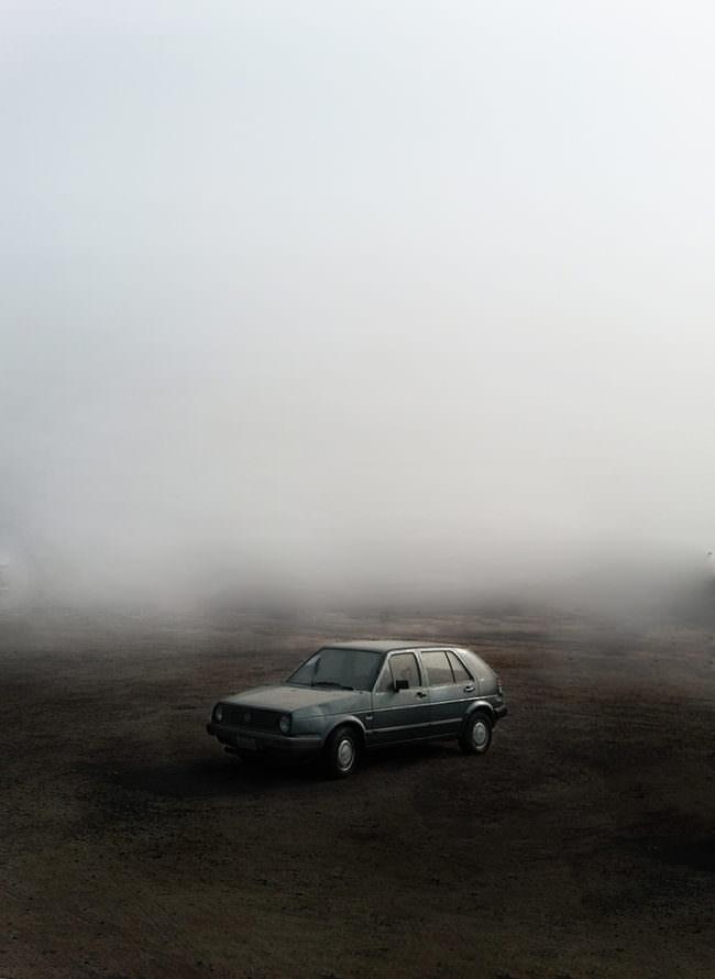 Ein Auto steht auf einem nebeligen Feld.